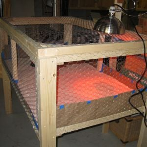 "The brooder pen is constructed from 2x2s and 2x4s with 1/2"" hardware cloth on the bottom and 1"" chicken wire for the sides and top.  The whole top is hinged.  I would make the top in two halfs next time for easier access.  I used rosin paper on the floor with about 1"" of sand on top of that. Sand was cheap and easy to clean."