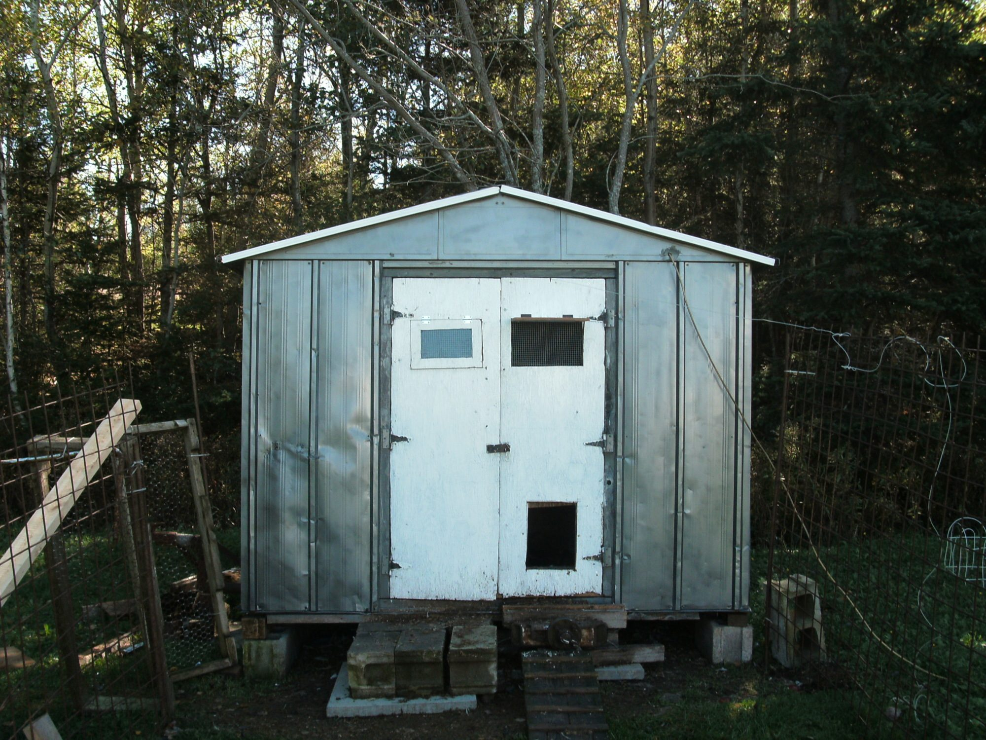 Old metal 4x8 shed I salvaged, painted, put wooden doors on, insulated and converted into chicken coop. Still a work in progress. It was basically a box kite when I drug it home.