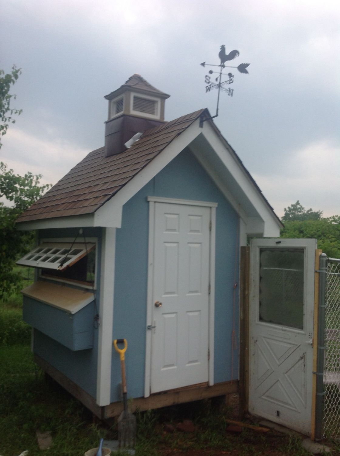 Final touch on the coop with a weather vane. Started the run with an old screen door and used chain link fencing.
