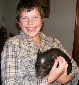 Joshua with our first piglet!